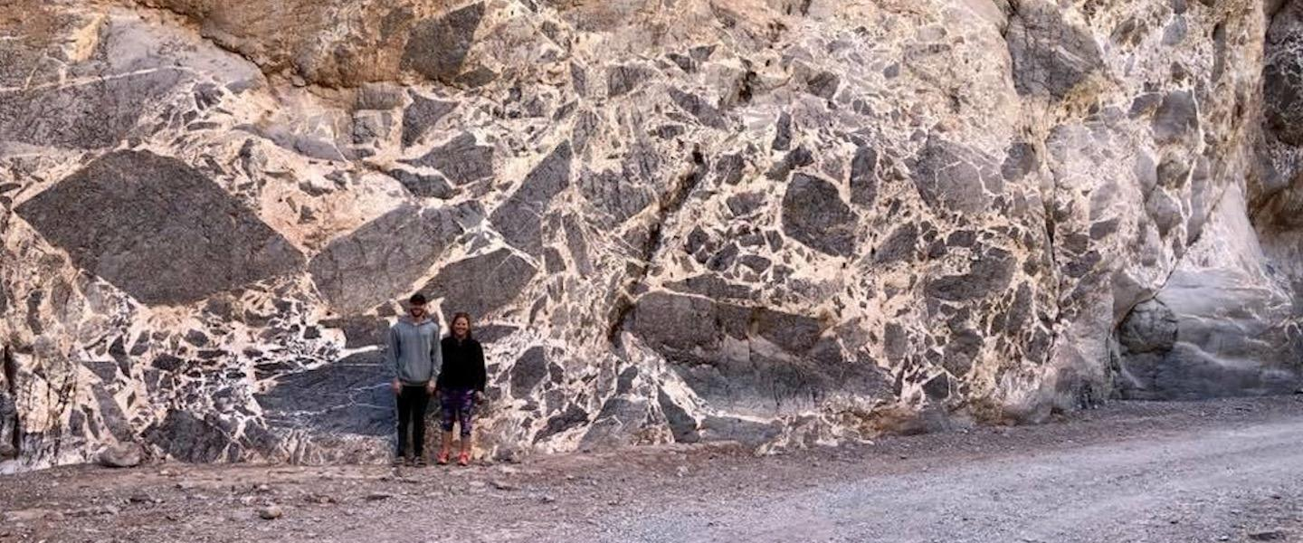 Two students standing by a large breccia outcrop